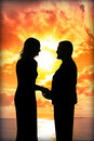 Young loving couple holding hands in silhouette at sunset gazing into each others eyes Royalty Free Stock Photos