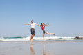 Young loving couple joyfully jumps on a tropical beach Stock Image