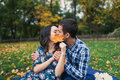 Young loving couple kissing behind big leaf, hidden kiss Royalty Free Stock Photo