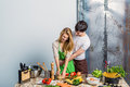 Young loving couple kitchen bunch vegetables Royalty Free Stock Photos