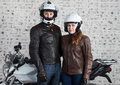 Young loving couple in a motorcycle outfit and helmets standing together near the street motorbike in the garage Royalty Free Stock Photo