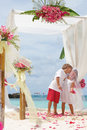 Young loving couple on wedding day in beautiful setup with flowers tropical beach and sea background Stock Image