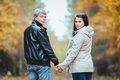 Young loving pregnant couple walking in the autumn park women and her husband Stock Photos