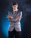 Young magician in suit on a dark background Royalty Free Stock Photo