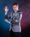 Young magician in suit on a dark background Royalty Free Stock Image