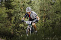 Young male athlete cyclists riding through forest Royalty Free Stock Photo