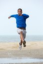 Young male athlete running at the beach and jumping man exercising outdoors Stock Photo