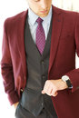 Young male burgandy blazer model checking his watch wearing a three piece suit Stock Photography