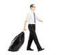 Young male carrying a garbage bag and walking full length portrait of isolated on white background Royalty Free Stock Images