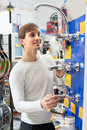 Young male choosing faucets in hypermarket smiling customer looking at modern Stock Images