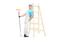 Young male decorator holding a paint roller full length portrait of and leaning on wooden ladder isolated on white background Stock Photography