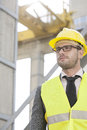 Young male engineer wearing hard hat looking away at construction site Royalty Free Stock Photo