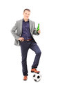 Young male football fan holding a beer full length portrait of and standing with ball under his foot isolated on white Stock Photo