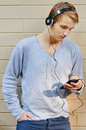 Young male going through song list scrolling with sun highlighting mp player Royalty Free Stock Image