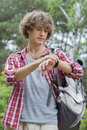 Young male hiker checking the time in forest Stock Image