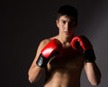 Young male kickboxer handsome caucasian wearing red boxing gloves and kickboxing gear isolated on a neutral background Stock Photo