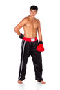 Young male kickboxer handsome caucasian wearing red boxing gloves and kickboxing gear isolated on a white background Royalty Free Stock Photo