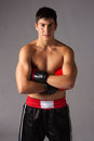 Young male kickboxer handsome caucasian wearing red boxing gloves and kickboxing gear on a neutral background Royalty Free Stock Photography
