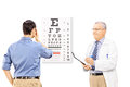 Young male patient taking eyesight test and an optician holding a clipboard isolated on white background Royalty Free Stock Photography