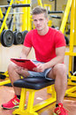 Young male personal trainer holding clipboard sitting on training equipment in gym Stock Photos