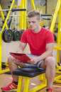 Young male personal trainer reading from clipboard writing on with training equipment behind him in gym Stock Image