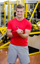 Young male personal trainer writing on clipboard smiling with training equipment behind him in gym Royalty Free Stock Photos