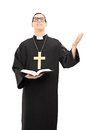 Young male priest praying to god vertical shot of a and holding a bible isolated on white background Stock Photo