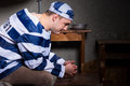 Young male prisoner wearing prison uniform has lost in thought w