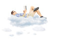 Young male reading a novel and lying on clouds isolated white background Stock Photography