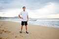 Young male runner dressed in the white t-shirt standing on the sand resting after intensive morning jog Royalty Free Stock Photo