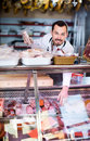 Young male shop assistant demonstrating sausages in butcher's Royalty Free Stock Photo