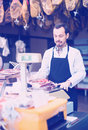 Young male shop assistant using scales for meat in butcher's s Royalty Free Stock Photo