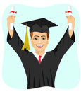 Young male student holding two diplomas with both hands on graduation day