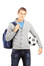 Young male student with school bag holding a football isolated on white background Royalty Free Stock Photos
