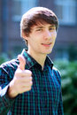 Young male student smiling with thumbs up against university building Stock Photos
