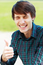 Young male student smiling with thumbs up against university building Royalty Free Stock Photography