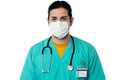 Young male surgeon wearing a face mask physician covering with surgical Stock Image