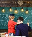 Young male teacher guides his child student to learning while boy hugs teacher, sitting in classroom, chalkboard with Royalty Free Stock Photo