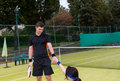 Young male tennis player helps his female partner to stand up Royalty Free Stock Photo
