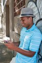 Young male using the cellphone model is wearing a hat Royalty Free Stock Images