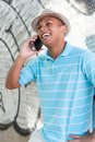Young male using the cellphone model is wearing a hat Stock Photo