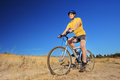 A young male with yellow shirt and helmet riding a mountain bike outdoors Stock Image