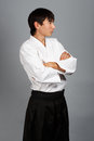 Young man in aikido uniform in serious pose standing on grey background Royalty Free Stock Photo