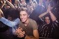 Young man amidst crowd enjoying at nightclub Royalty Free Stock Photo