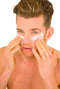 Young man applying lotion on her face white background Stock Photography