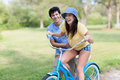 Young man assisting young woman on bike latin men in shorts and blue shirt helps women riding blue with green trees and grass Royalty Free Stock Images