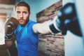 Young man athlete boxing workout in fitness gym on blurred background.Athletic man training hard.Kick boxing concept Royalty Free Stock Photo