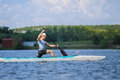 Young man athlete on rowing kayak on lake