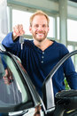 Young man with auto in car dealership beside a new obviously he is buying the or making a test drive and holding the keys hand Royalty Free Stock Photo