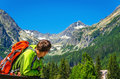 Young man with backpack looking at mountain peaks Royalty Free Stock Photo